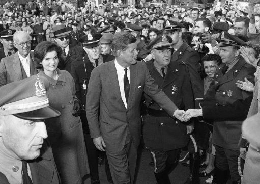 1960. Novembre. Peut être le 8 ou le 9. John F. Kennedy gets a congratulatory handshake. Left is his wife, Jacqueline. Behind Mrs. Kennedy is Amb. Joseph P. Kennedy.