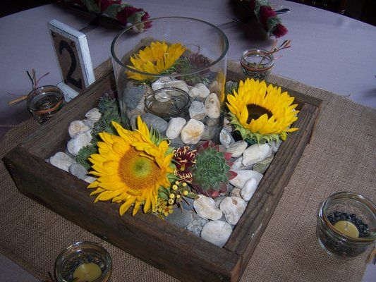 Sunflowers Succulents And River Rocks Surround A Candle