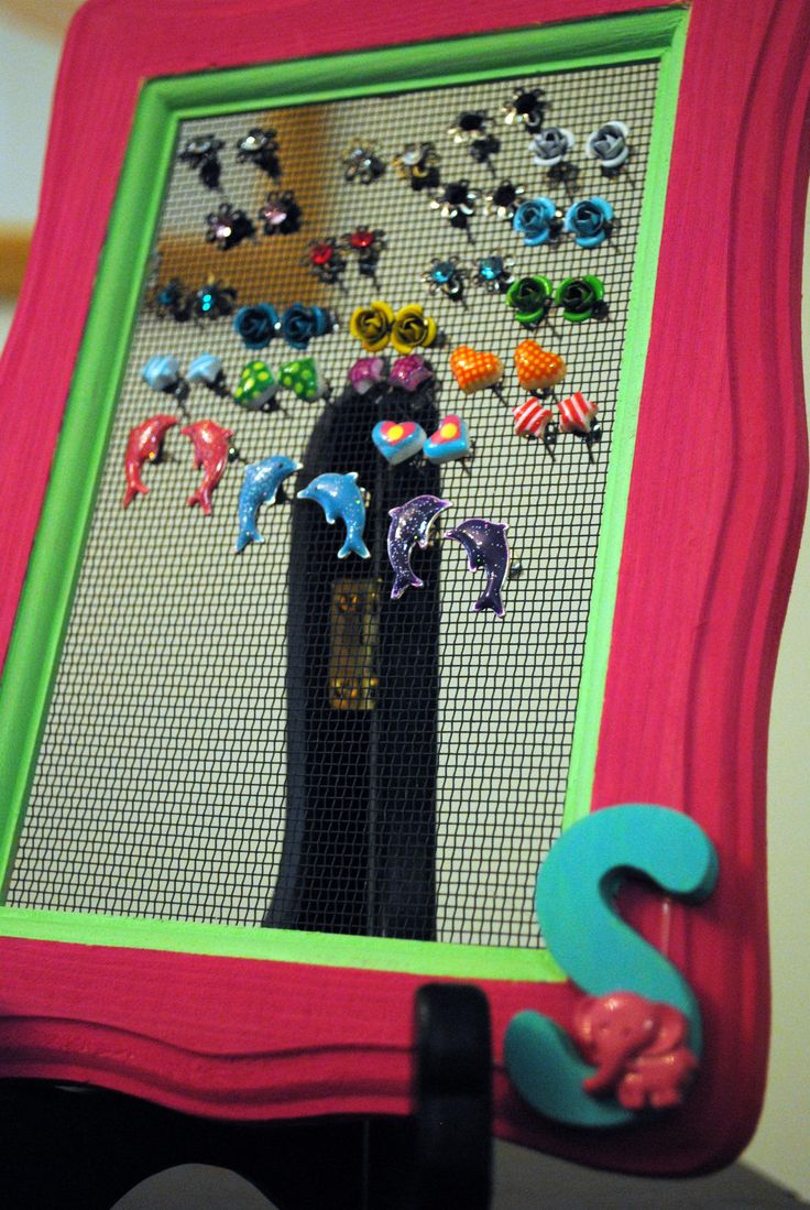 Earring holder for a little girl. Made from a picture frame and window screening