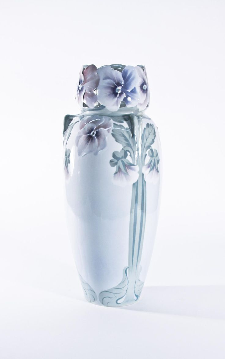 Height: 20 inches Swedish, circa 1900.  A monumental porcelain Rorstrand vase modeled with pansies. The tall cylindrical form has a waisted neck with a rim modeled as open-face pansies, with flowering stems flowing down the white ground body of the vessel.