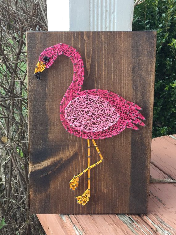 """This listing is for a Flamingo string art sign. This sign would be perfect for a nursery, children's room, or any animal lover! This sign measures approximately 9.25"""" x 14"""". Boards can be stained with Special Walnut, Dark Walnut, or Classic Gray (examples above). Please include color choice in note to seller. If no stain color is chosen, board will be stained with Special Walnut. You may choose up to two string colors for the flamingo in addition to the black and yellow accent colors…"""