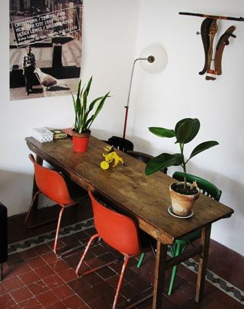 orange chairs wooden table white walls house plants and vintage tile