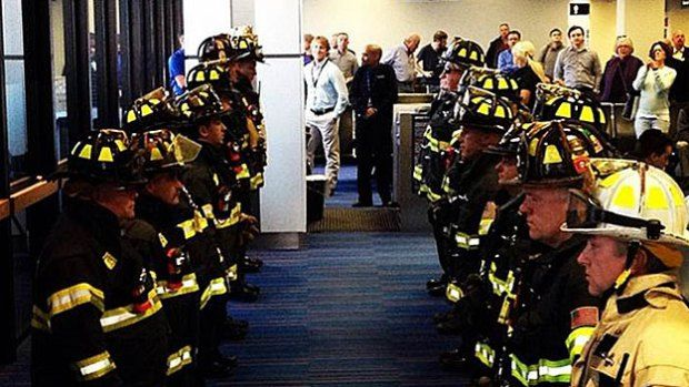 A group of MassPort firefighters waits for the family of a fallen Boston firefighter. (Photo credit: Max Widmer)