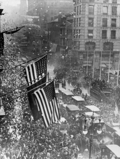 View of a crowded New York City street as people celebrate Armistice Day on November 11, 1918, marking the end of World War I.