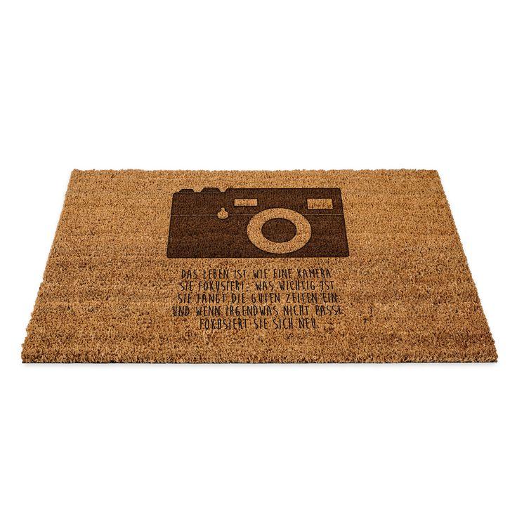 Fußmatte Kamera aus Fussmatte Kokos  Natur - Das Original von Mr. & Mrs. Panda.  Eine wunderschöne Fussmatte Kokos aus dem Hause Mr. & Mrs. Panda - Die Fussmatte wird sehr aufwendig graviert. Dieses besondere Fertigunsverfahren mit Naturmaterialien wurde von uns entwickelt und ist einzigartig.    Über unser Motiv Kamera  Diese Retro-Kamera gefällt bestimmt nicht nur professionellen Fotografen, sondern lässt auch jedes Hobbyfotografen-Herz höher schlagen.    Verwendete Materialien  Die…