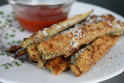 Baked Parmesan Zucchini Sticks  3 large zucchini, sliced longways, halved and cut into sticks   2 eggs   1/2 cup plain bread crumbs   1/4 cup Parmesan cheese, grated   1 tsp dried oregano   1/2 tsp dried garlic powder   Olive oil spray