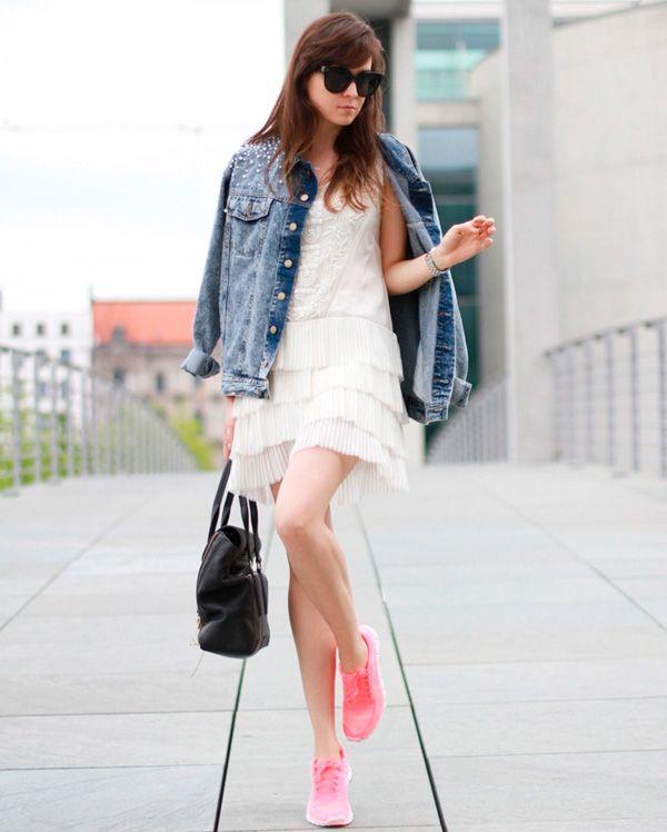 Look com vestido branco de babados, jaqueta jeans e tênis rosa.