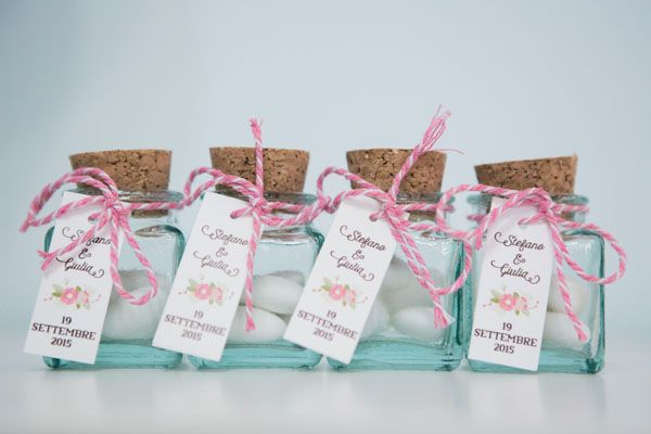 jordan almonds in glass bottles favors | photo: fibre di luce http://weddingwonderland.it/2016/03/matrimonio-rustico-colori-pastello.html