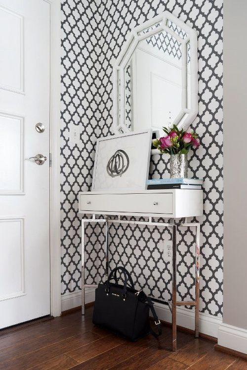 decoração de hall de entrada com papel de parede preto e branco, aparador branco com pés de metal, poster abastrato e espelho