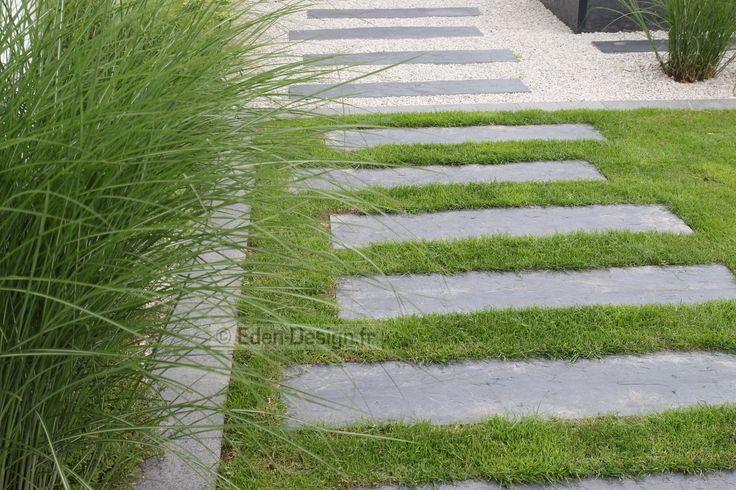 Allée de jardin en pas japonais en ardoise. L'allée passe du gazon à la zone en gravillons.