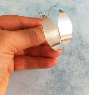 """Coleção """"Bamboo""""  Brincos de prata produzidos manualmente. Argolas de prata com chapa em forma de folha. Brincos minimalistas muito leves e confortáveis. **Oferta das molas de segurança.  Tamanho:  Diâmetro - 4,5cm Largura da folha - 1,2cm  Cor: Prateado  ----------------------------------------  """"Bamboo"""" Collection  Handmade sterling silver earrings.  Silver hoop with plaque-shaped leaf. Minimalist earrings very light and comfortable. ** Offer the safety catch.  Size: Diameter - 4.5 cm…"""