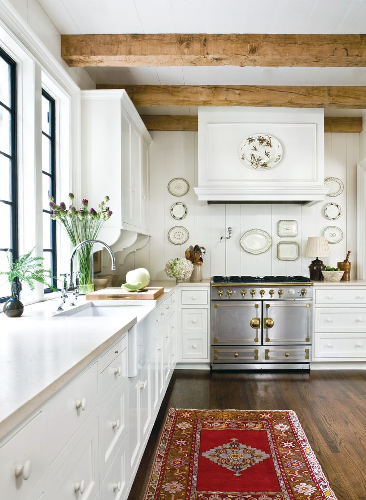Love the stove..dark wood floors, lighter wood beams...white/cream cabinets