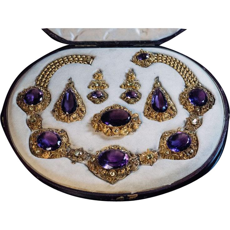 This magnificent antique parure from the late Georgian era, circa 1830, features large faceted amethysts accented by green chrysoberyls set in ornate