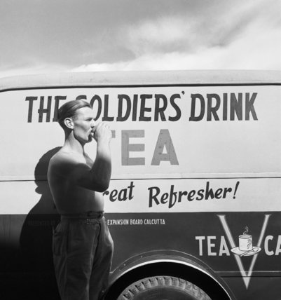 Cecil Beaton photograph of a British soldier drinking tea next to a Red Cross mobile tea wagon at Calcutta airport in 1944.  Beaton Cecil  © IWM (IB 1882)