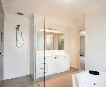 Walk-in shower with glass side-panel, recessed tiled shelf, & smart-tile floor waste.  Corner spa bath.  Feature wall tiled as floor tile.