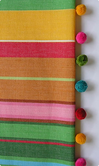 I like the idea of the multi coloured pom pom trim, however on a plain natural material!