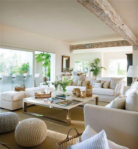 Salón luminoso en tonos beige con vigas en el techo