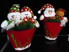 Muñecos navideños de felpa dentro de macetas.