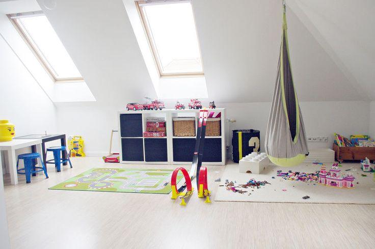 Przestrzeń pod skośną ścianą w tym dziecięcym pokoju zagospodarowano pojemnikami i regałem do przechowywania zabawek. Dywany nie tylko zdobią pokój i dodają mu przytulności, ale też zapewniają wygodę podczas zabawy na podłodze. Zamiast fotela do wypoczynku służy huśtawka z miękkim siedziskiem.