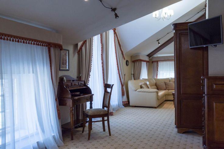 Номер люкс просторный, с большим диваном, винтажной мебелью и шкафами, наполненными книгами
