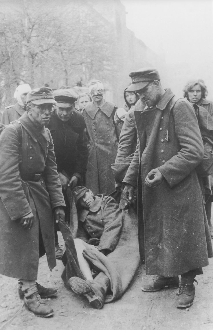 After the battle: German soldiers carrying a wounded comrade and Berlin civilians in the streets of the devastated capital, May 1945.