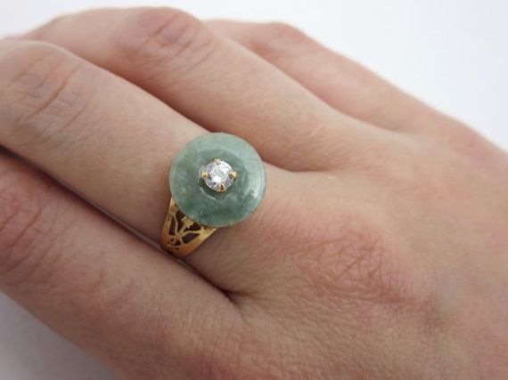 A unique vintage jade ring, featuring a genuine nephrite jade disc, with a clear glass stone accent, in 14k gold. Marked, but I cannot make it out. Acid tested at 14k. About a US size 6.25. Jade is tested with a Presidium Gem Tester. Actual packaging will vary depending on item/s