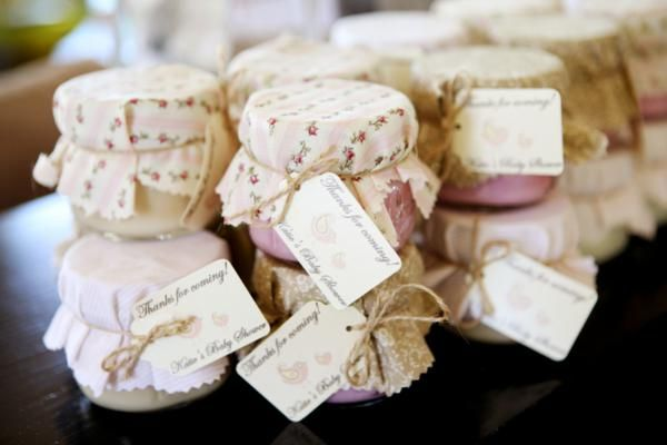 Homemade candles from small mason jars, covered with fabric and jute.  Cute favors!