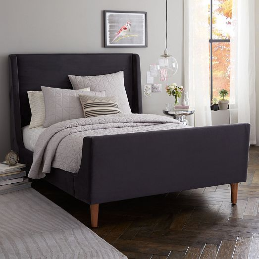 NEW! Our modern take on a classic sleigh bed features lofty solid wood legs and crisp edges that emphasize the gentle curve of the wings. Fully upholstered on all sides, its equally at ease against a wall or floating in the middle of a room.