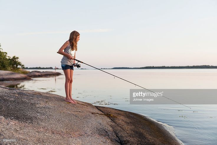 Girl fishing in sea, dusk : Stock Photo