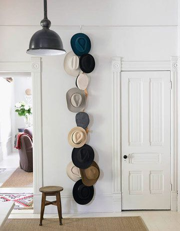 Vertically hung accordian wood hanger OR We've been needing a place for hats lately. We have way too many. I'm thinking a 3M hook, hanging a belt from that, and clothespinning the hats to that.