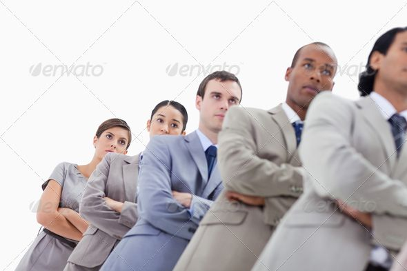Low-angle shot of colleagues crossing their arms in a single line with focus on the last two women ...  20s, 30s, Focused Shot, Isolated Color, Mid Adult, Studio Shot, arms folded, black, businesspeople, caucasian, close-up, colleagues, copy space, crossed, female, full suit, hispanic, in order, looking away, low angle view, male, man, mixed-race, portrait, professional, serious, single file, standing, teamwork, togetherness, well dressed, white background, woman, young adult