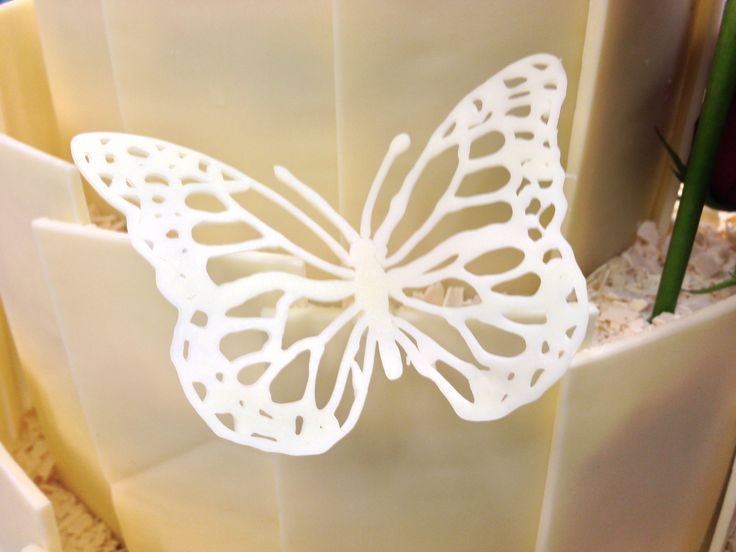 Delicate hand piped white chocolate butterfly for a wedding cake