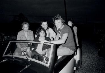 MICHEL GINFRAY (NÉ EN 1946)  Johnny Hallyday avec Serge Gainsbourg, Jane Birkin, Coluche, Gérard Lenorman et Dani dans la 'Rosengard' modèle 1939 (retapée par ses amis) qu'il a reçue en cadeau, à Thoiry, le 16 juin 1976 pour son 33ème anniversaire. 1976