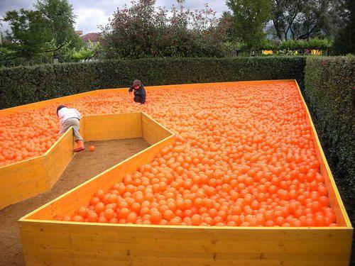 """L'idea: Abbiamo interpretato il tema del Festival """"L'energia nel giardino"""" come una riflessione sulla gratitudine e meraviglia per la generosità della natura. Una singola pianta, un arancio (Citrus x sinensis), è posizionato al centro del giardino, ai suoi piedi 50.000 arance (sfere di plastica), la somma dei raccolti di 100 anni di una singola pianta."""