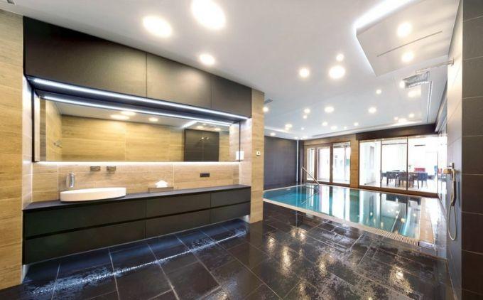 Protože je bazén součástí interiéru, hledal designér s majiteli prvky a vybavení, které prostředí maximálně zútulní. K bazénu přímo přiléhá koupelna se smaltovaným umyvadlem (Alape), otevřenou sprchou (Grohe) a nechybí ani klozet