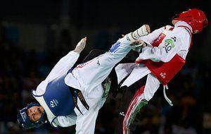 Phannapa Harnsujin of Thailand kicks Kimia Alizadeh Zenoorin of Iran in the women's under-57kg Taekwondo repechage.