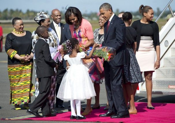 A boy and a girl present flowers to President Obama and first lady Michelle Obama upon the arrival of Air Force One at Julius Nyerere International Airport in Dar es Salaam, Tanzania.