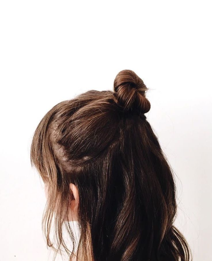 medium brown hair tied in a messy man bun, the shorter pieces near the front falling out