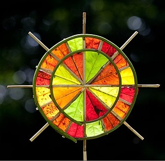 ''Rainbow Sun Wheel'' by Richard Shilling, a ''land artist''. This piece was created with sections of Spring leaves pinned to a Dogwood frame with thorns, positioned to catch the evening sun & reveal the leaf colours of Spring.