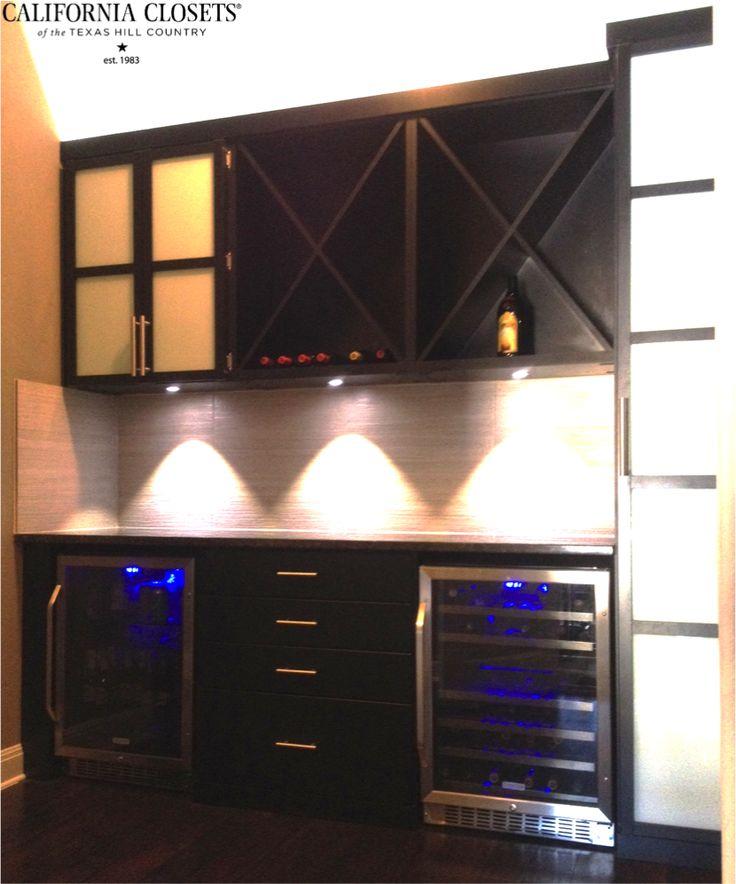This slick black wine bar features custom doors with milky glass inserts, chrome hardware, fascia trim, wine X's, integrated LED lighting, & granite countertop. #Austin #CaliforniaClosets #custom #design #wine