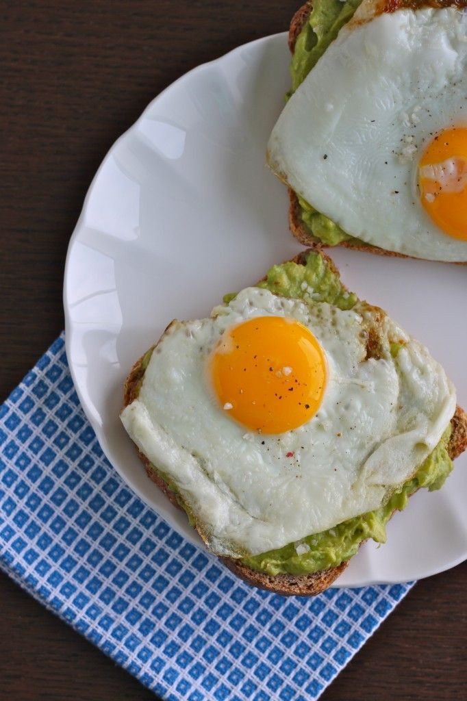 Multi-grain bread with a thick coating of mashed avocado, topped with a delicate, yolky sunnyside egg