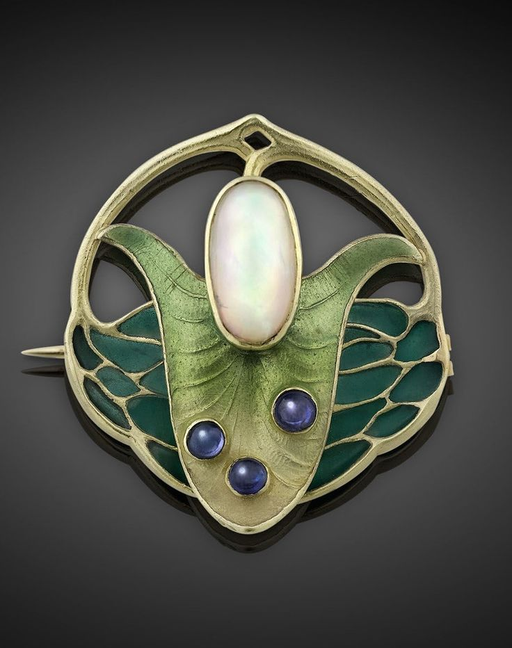 An Art Nouveau gold, opal, sapphire and emamel brooch, by Theodor Fahrner, circa 1890. In the form of a flower, centring a white opal, highlighted by green enamels and three sapphire cabochons, mounted in 18k gold.