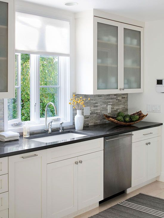 """Glass-Front Cabinet Doors """"Glass-front cabinets ensure a small kitchen remains light, airy, and inviting. If you don't like the idea of having your dishware on display, frosted glass-front doors have a similar effect but can obscure any mismatched contents."""""""