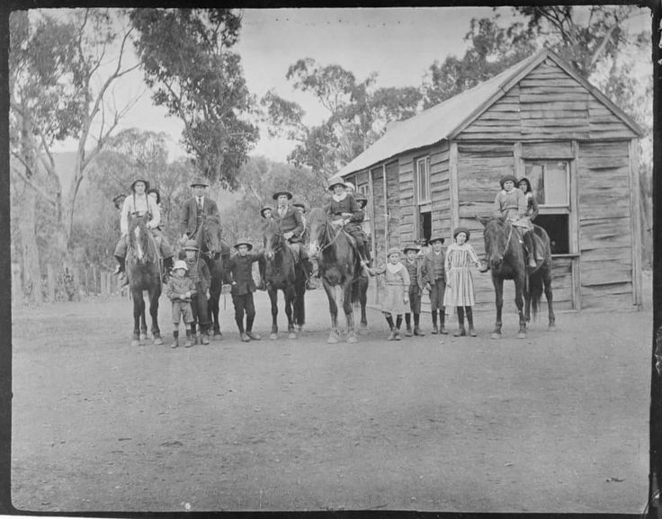 "Country School, Gippsland, 1915. How many children ride a horse to school, today? The following information is inscribed on the verso: ""John Jackson photographer, Talbotville via Stratford. A small school with group of scholars; situated about one and a half miles below Alex Guy's homestead on the same side of the Pioneer River, by the old hill track route. The schoolmaster is second from the left, on the horse, and this photo was taken in 1915, and this school was closed up about 1924.""…"