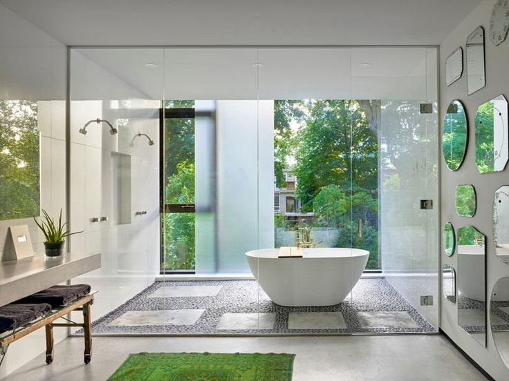 In this bright bathroom, a sliding frosted glass privacy panel can be used when needed, and vintage mirrors collected by the home owner cover the wall.