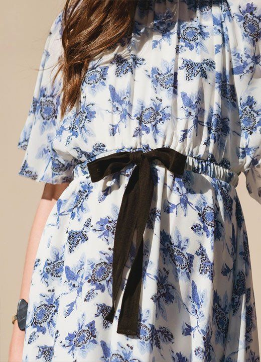 A flouncy little dream of a dress in a blue and white floral print. Cinched in at the waist with a black grosgrain ribbon tie. keyhole with button detail at th