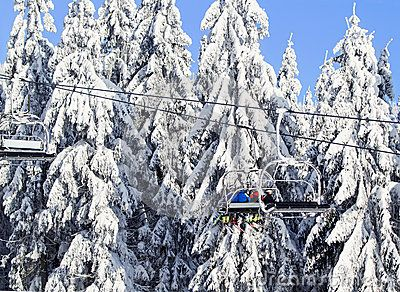 Ski lift on beautiful  winter day ,against the backdrop of snow-covered fir trees.