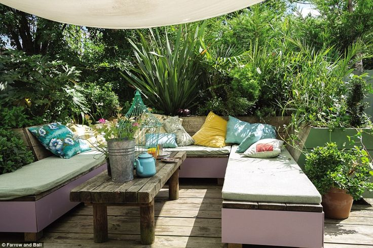 A bohemian seating area in  Dorset, features subtle pink and green shades of Farrow & Ball paint to complement the lush surroundings