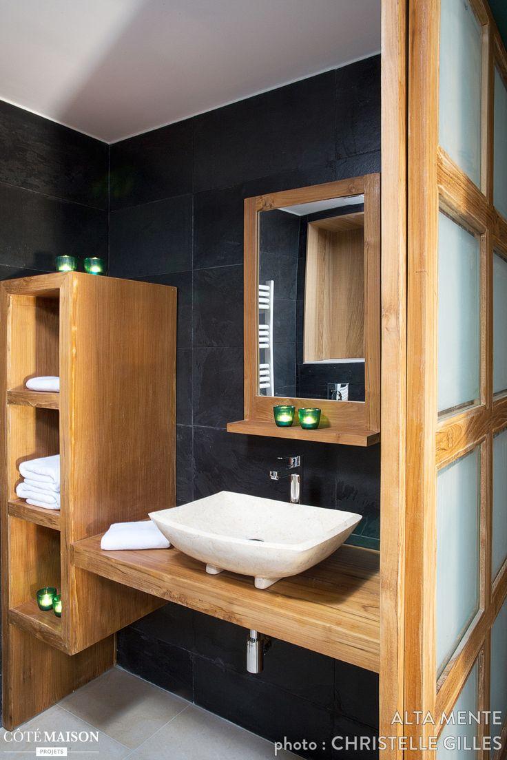 De la chaleur et de la retenue dans cette salle de bains. Rangements muraux en bois. Murs noirs. Sol gris.