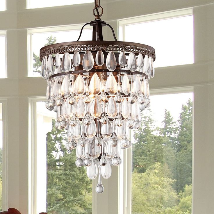 With an elegant antiqued-bronze finish and stunning rows of crystals placed in the shape of an inverted pyramid, this Martinee chandelier shows your taste for elegance and refinement. Four lights brighten up any indoor space.